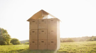 Stack of cardboard boxes on a meadow against sky, a house made of cardboard boxes