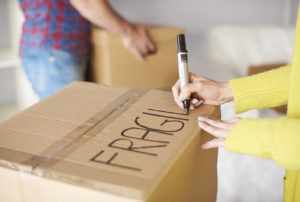 Young couple moving home, young woman labelling cardboard box, mid section