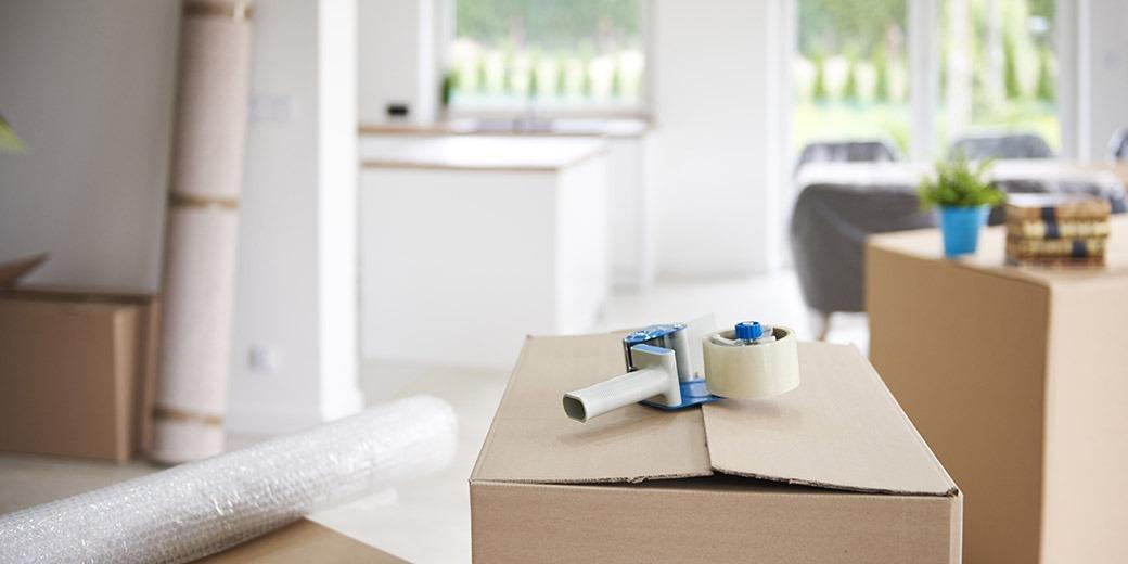 Tape gun on cardboard box