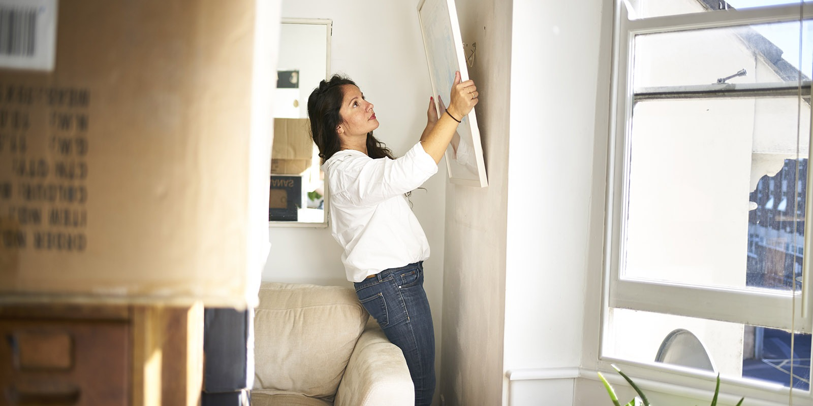 Woman taking a picture off the wall ready to pack while moving house