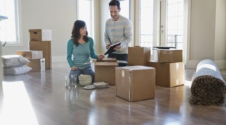 Couple surrounded by cardboard boxes look at moving checklist