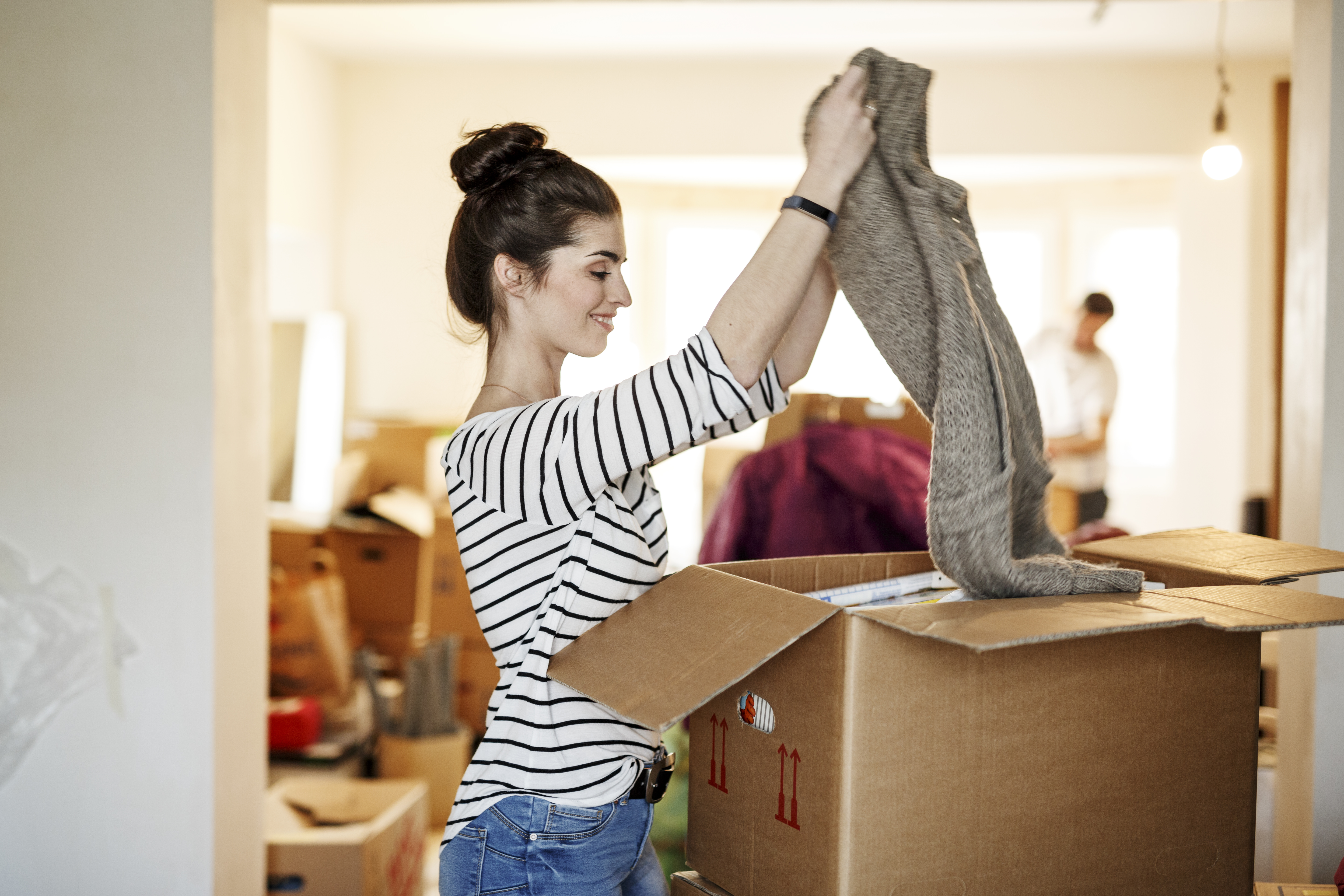 Young woman packing clothing into a box with handles cut into the sides