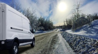 a white moving van driving on a country road in the winter