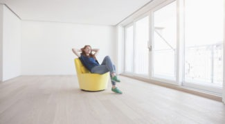 Young woman sitting on yellow armchair in her empty living room