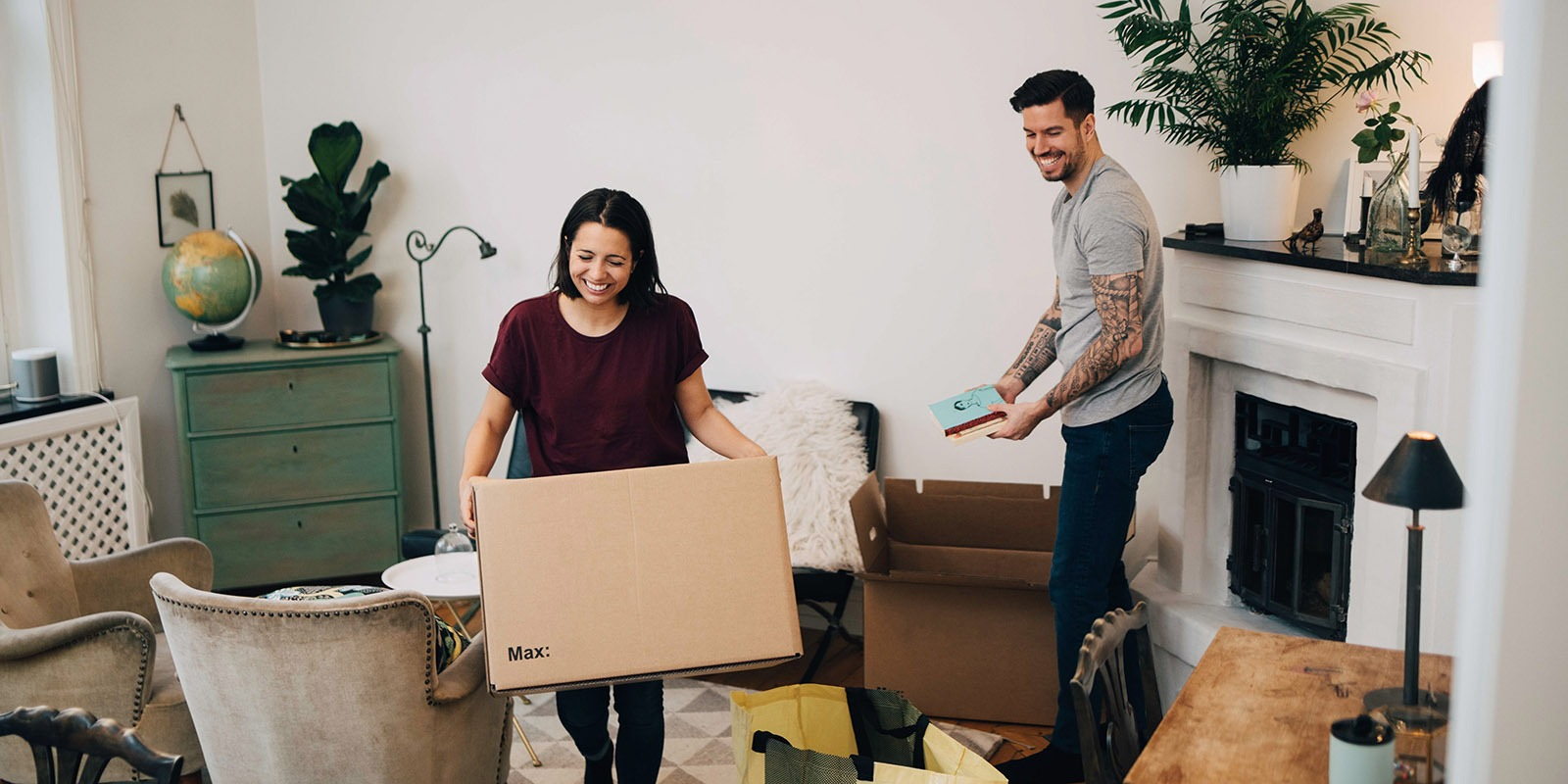 Happy couple unpacking boxes in living room at new home