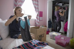 Mother and daughter organizing bedroom closet