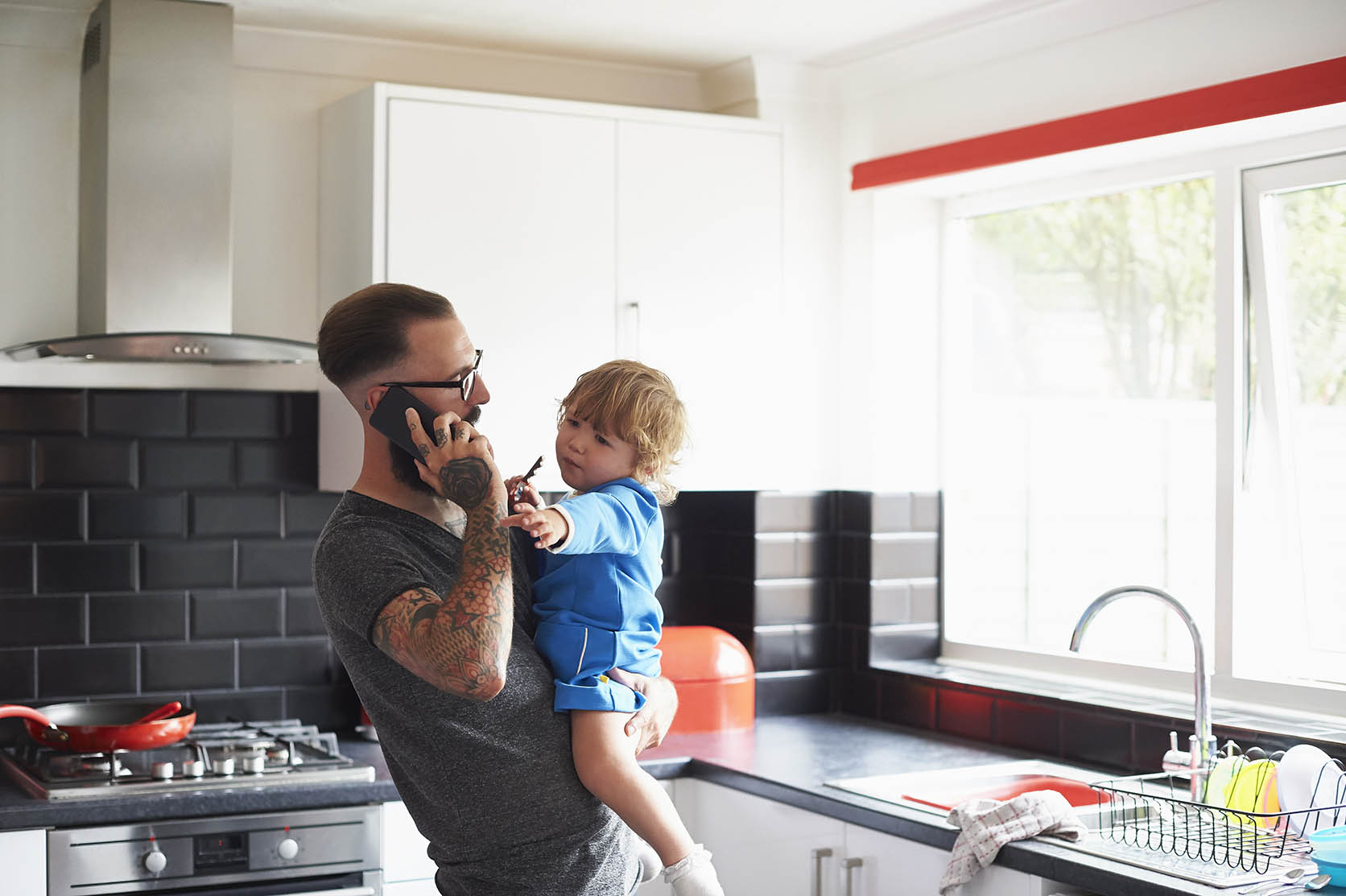 Young dad making phone call while holding a toddler