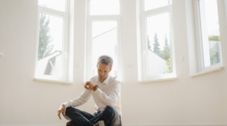 Man sitting on floor of his new home checking his watch