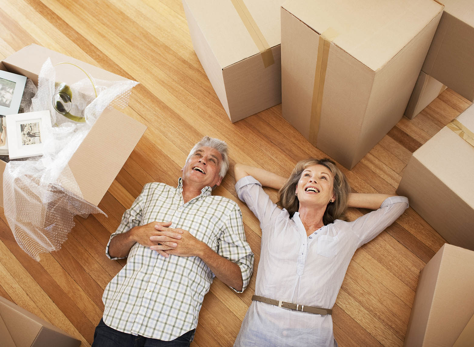 Happy older couple laying on floor surrounded by closed boxes