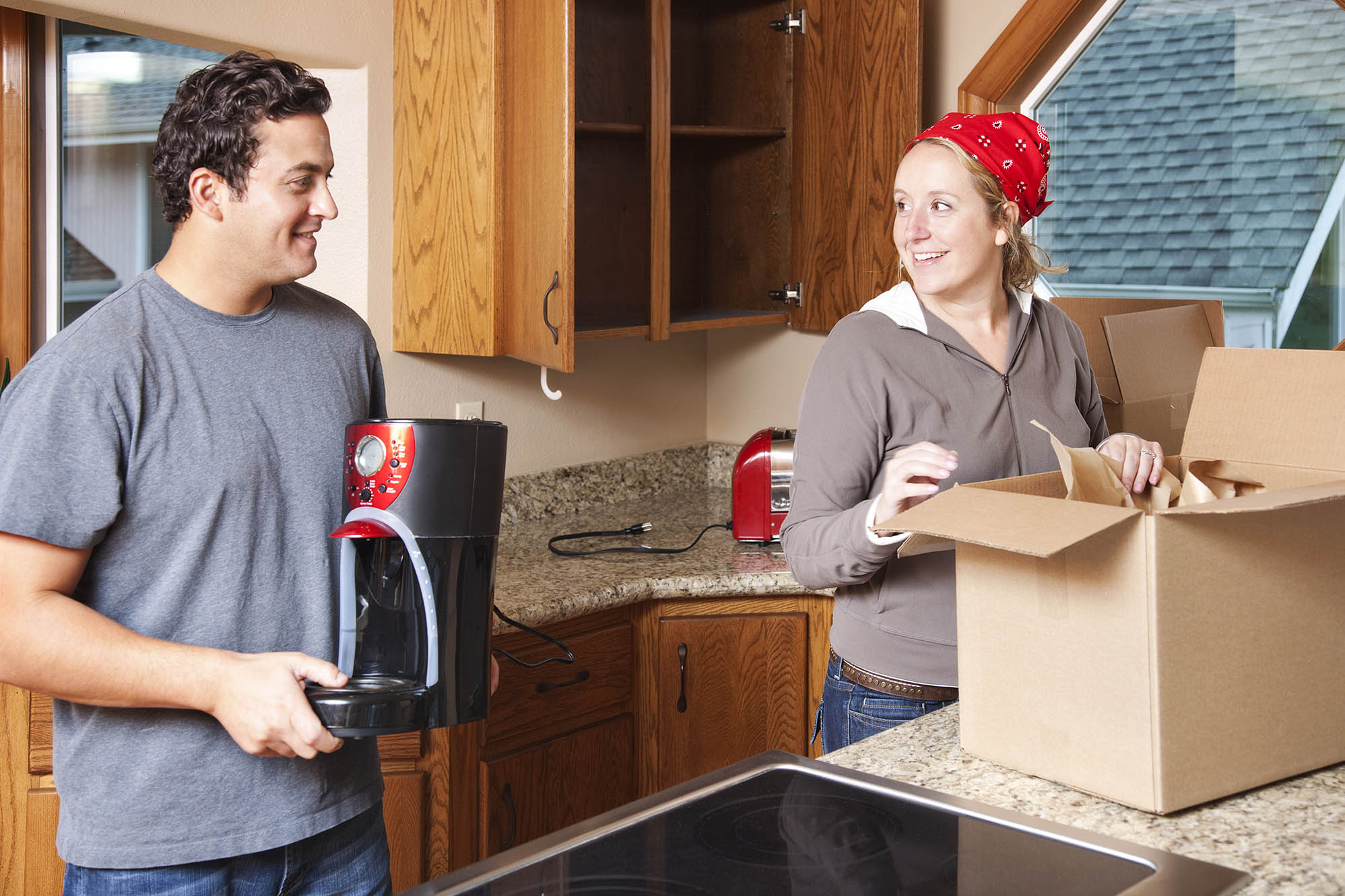 Two people packing appliances in a kitchen
