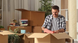 Smiling man packing his belongings