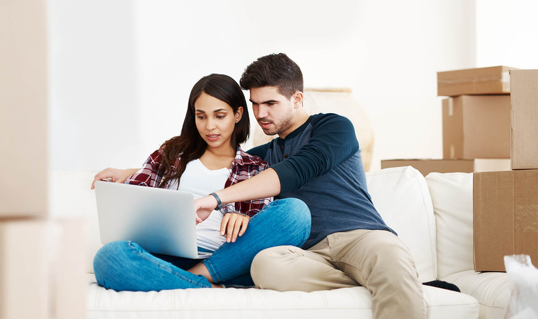 Shot of a young couple using their laptop to research movers