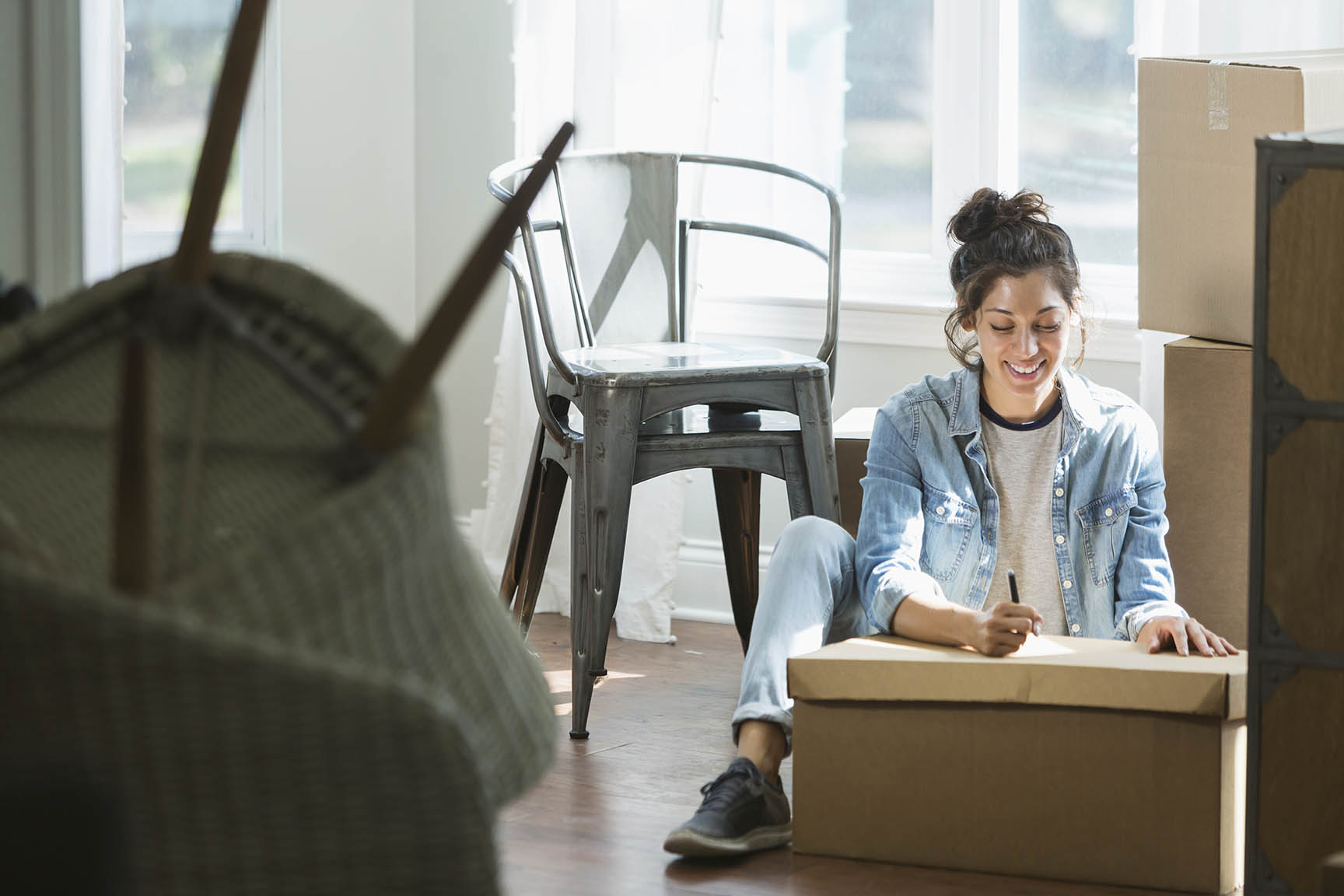 Woman writing moving checklist in her home surrounded by boxes