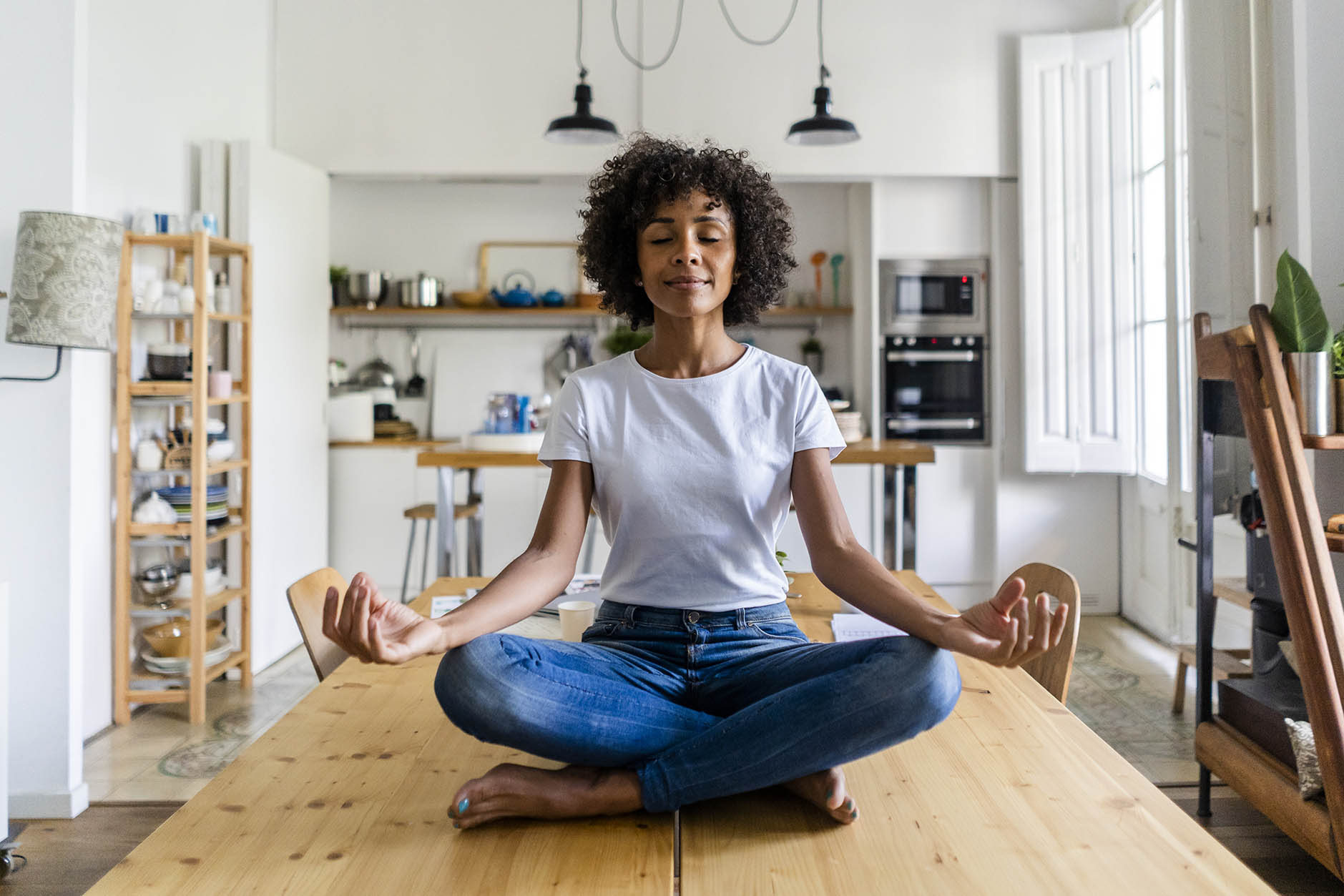 Smiling woman with closed eyes meditating on table at home