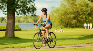 Woman Biking in City Park