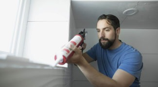 Man using caulk gun for home improvement project