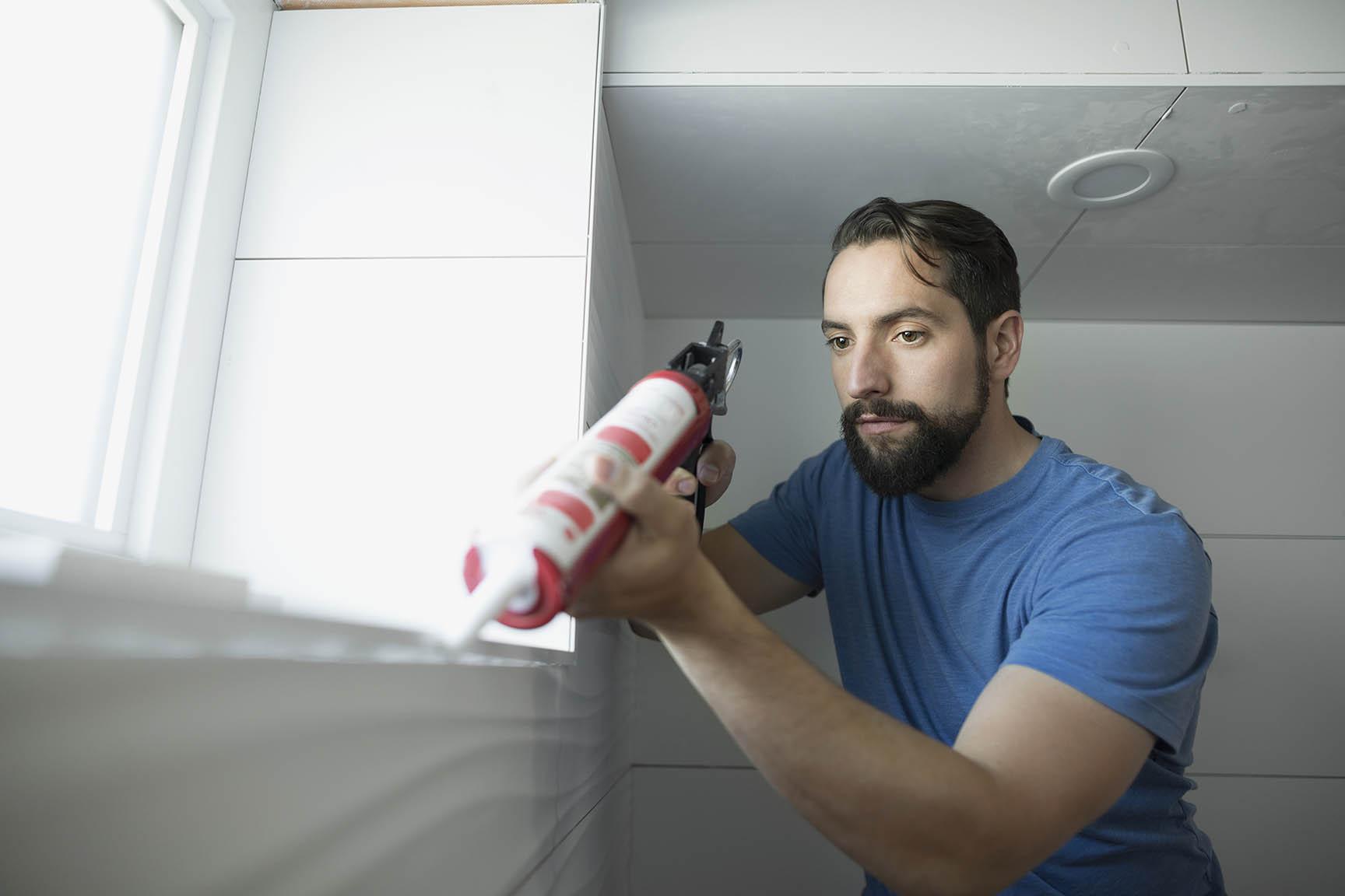 Man using caulk gun for home improvement project