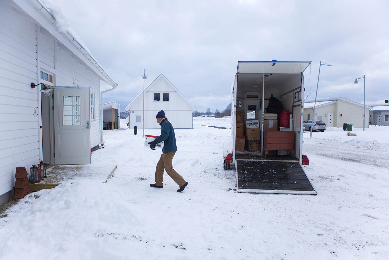 Man unloading boxes from moving truck in winter