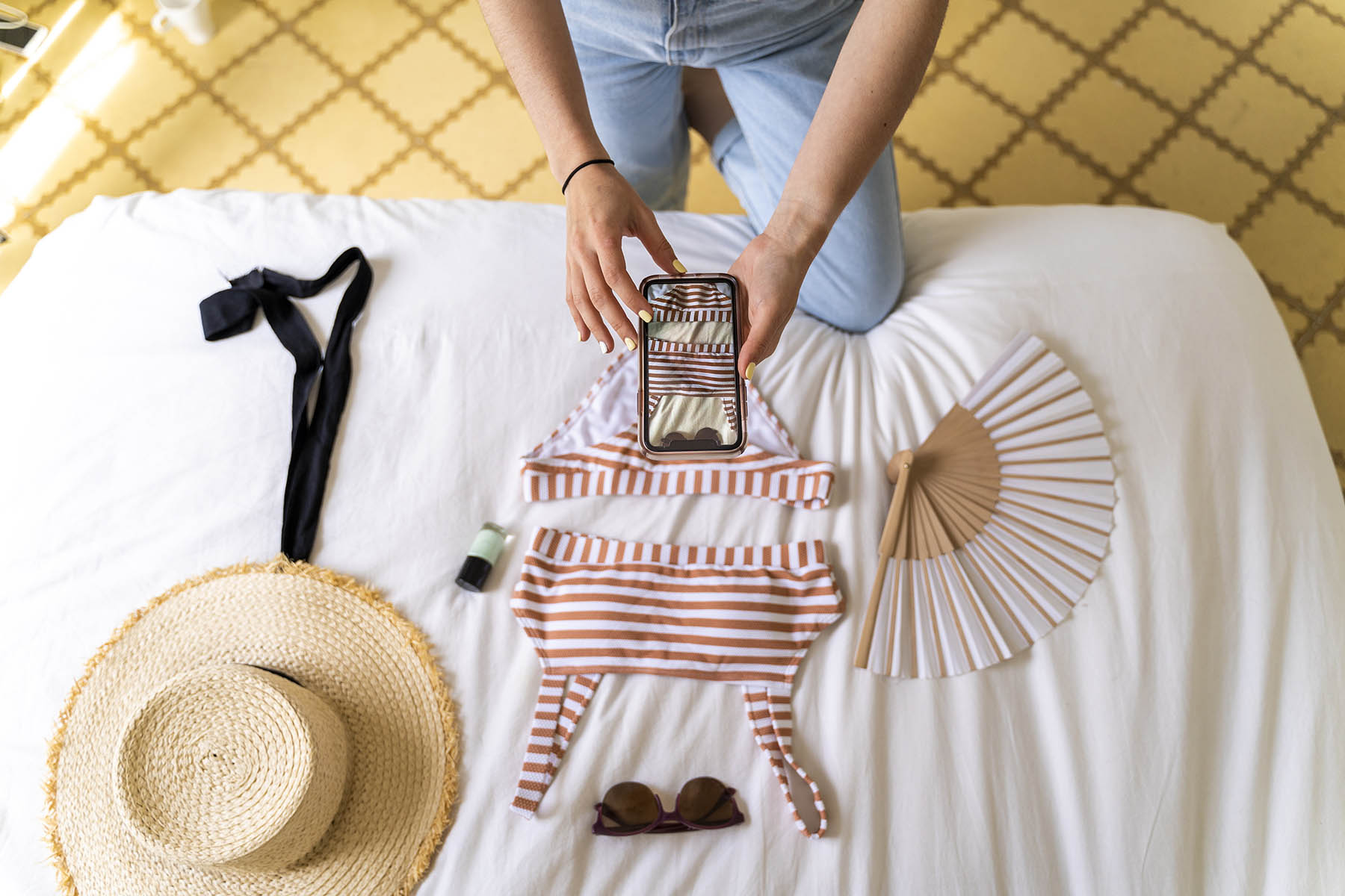 Woman taking picture of sale items laid out on bed