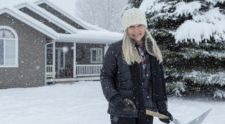 Woman shoveling snow in front yard