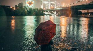 Woman holding red umbrella and facing bridge in downtown Minneapolis neighborhood