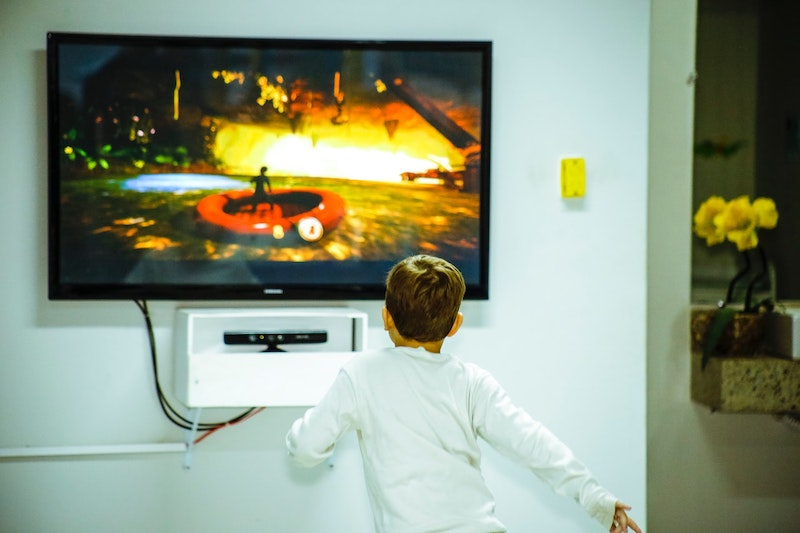 Young child playing in front of flat screen TV.