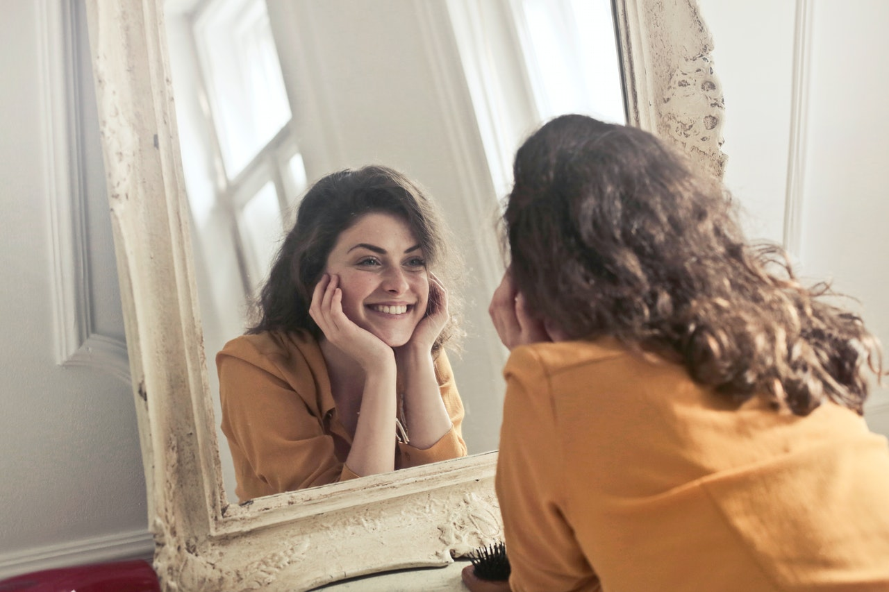 Woman smiling in mirror's reflection; how to pack a mirror
