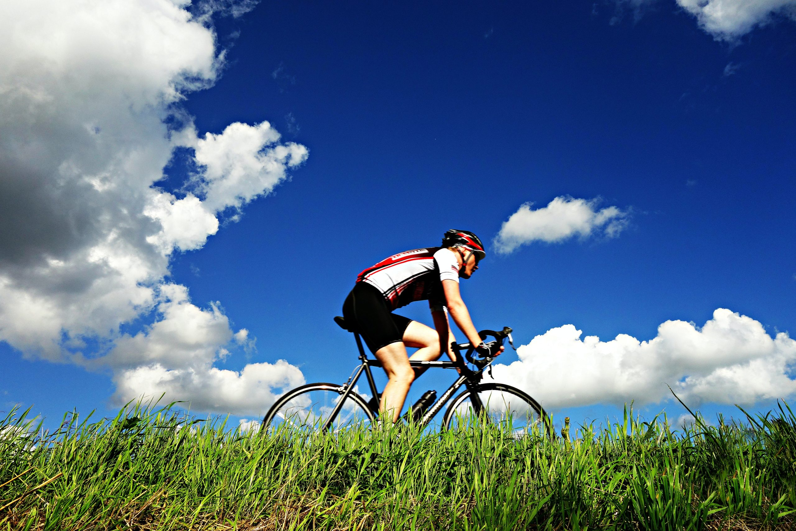 Man riding a bike under a blue sky.